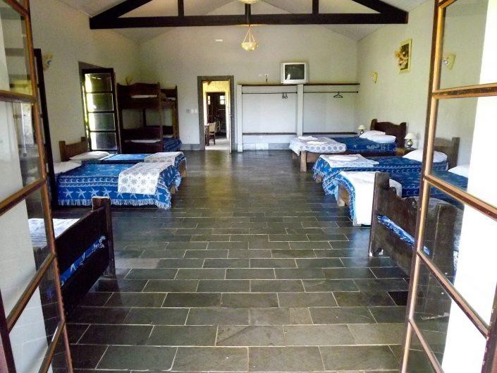 Quarto de uma das acomodações do hotel fazenda parque dos sonhos com, 5 camas de solteiro, duas de casal, uma beliche, televisão, cofre e frigobar