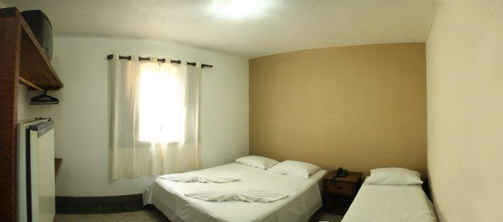 Quarto de um dos chalés do hotel fazenda parque dos sonhos com televisão, cama de casal e uma cama de solteiro, frigobar e cofre