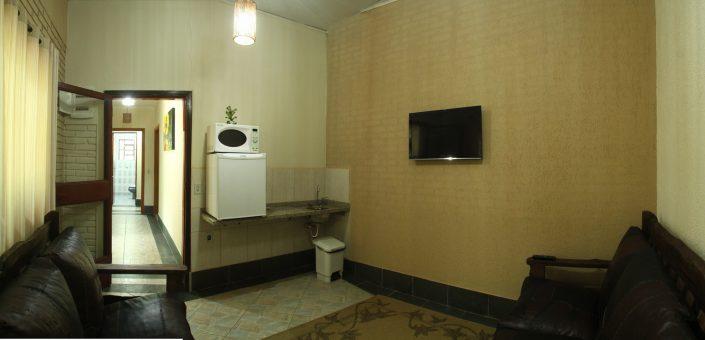 Sala de um dos chalés do hotel fazenda parque dos sonhos com sofás para descanso, tv de led, frigobar, microondas pia etc.