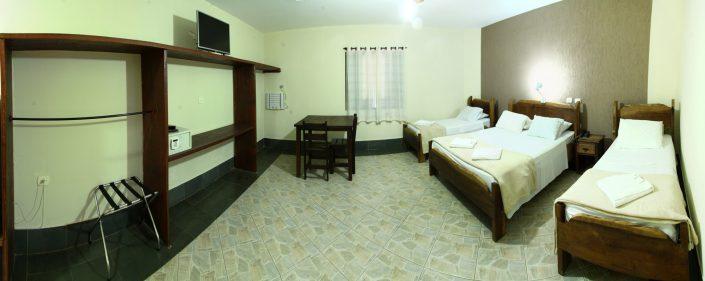 Quarto de uma das acomodações do hotel fazenda parque dos sonhos com, duas camas de solteiro, cama de casal, um berço, ar condicionado quente e frio, tv de led, cofre, frigobar
