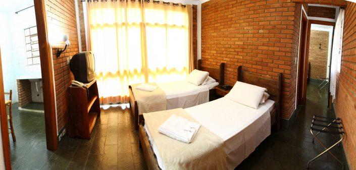 Quarto do chalé no hotel fazenda parque dos sonhos com duas camas de solteiro, televisão etc