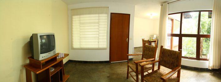 Sala de um dos chalés no hotel fazenda parque dos sonhos com, cadeiras, televisão e vista para o jardim