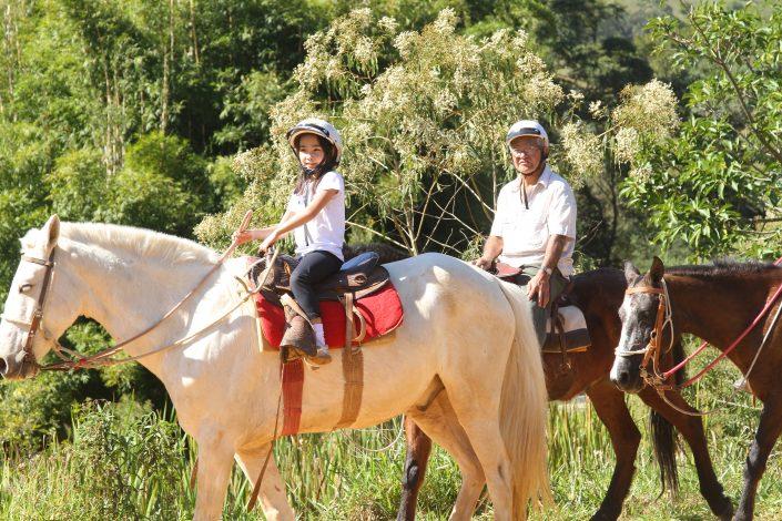 A Foto mostra uma criança pequena andando a cavalo, junto de um adulto