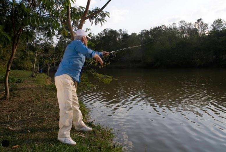 Homem lançando anzol para pescar peixes em um dos lagos do hotel fazenda campo dos sonhos