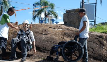 Usuário de cadeira de rodas sendo preparado para fazer a tirolesa do pânico no hotel fazenda parque dos sonhos