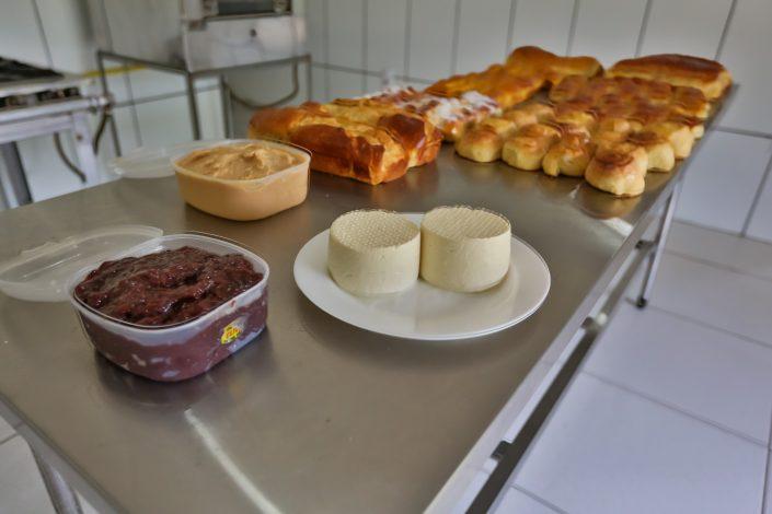 Mesa com vários tipos de pães caseiros, doces e salgados, bananada, doce de leite e queijo