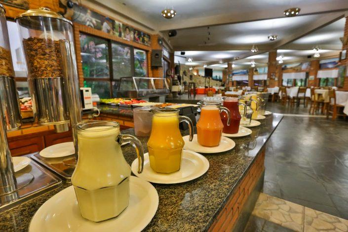 A foto mostra a mesa de sucos, saladas, cereais do café da manhã no hotel fazenda parque dos sonhos
