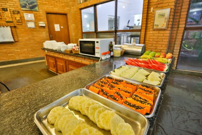 A foto mostra o restaurante do hotel fazenda parque dos sonhos com foco para a mesa de frutas, com frutas como, abacaxi, mamão, melão, melancia banana etc