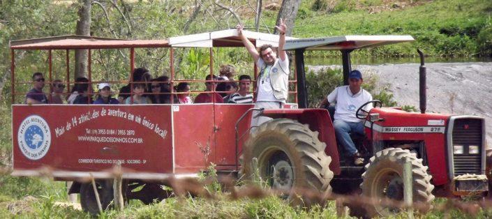 Pessoas subindo para a pedra grande no hotel fazenda parque dos sonhos, em uma carreta sendo puxada por um trator