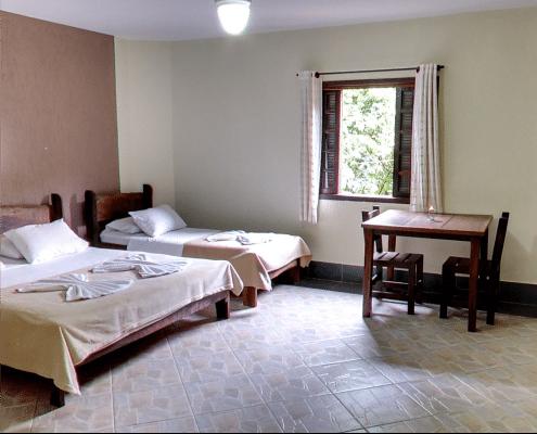 Foto do chalé do hotel fazenda parque dos sonhos, com, cama de casal, solteiro, e mesa com duas cadeiras