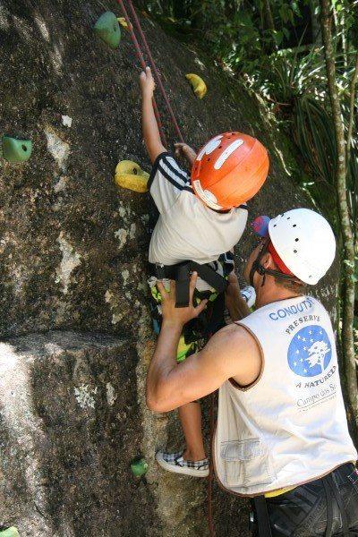 Criança pequena fazendo a escada kids no hotel fazenda parque dos sonhos, sendo auxiliada pelo condutor da atividade